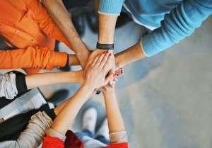 Top view image of group of young people putting their hands together. Friends with stack of hands showing unity.
