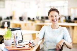 Portrait of happy female entrepreneur sitting at office desk. Horizontal shot.