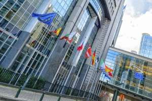 European Parliament in Brussels and a row of EU member states flags.