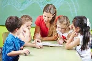 Nursery teacher reading book aloud to children in a kindergarten group