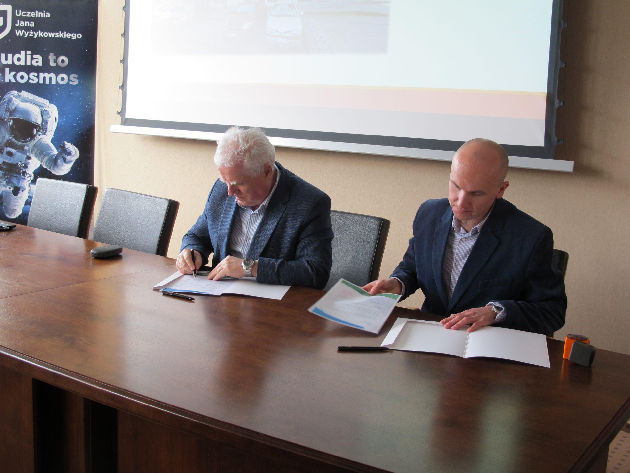 dwóch mężczyzn siedzi przy stole i podpisuje umowę o współpracy