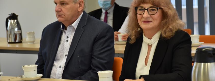 Pan i Pani przy stole siedzą piją kawę, kobieta się uśmiecha