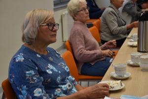 na zdjęciu kobiety siedzące przy stole pijące kawę