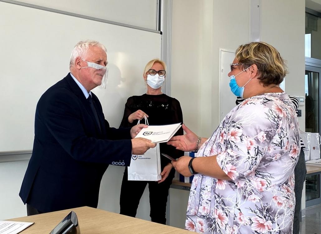 kobieta odbiera nagrodę odmężczyzny woddali druga kobieta podaje upominek mężczyźnie