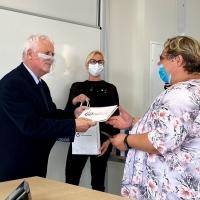 kobieta odbiera nagrodę od mężczyzny w oddali druga kobieta podaje upominek mężczyźnie
